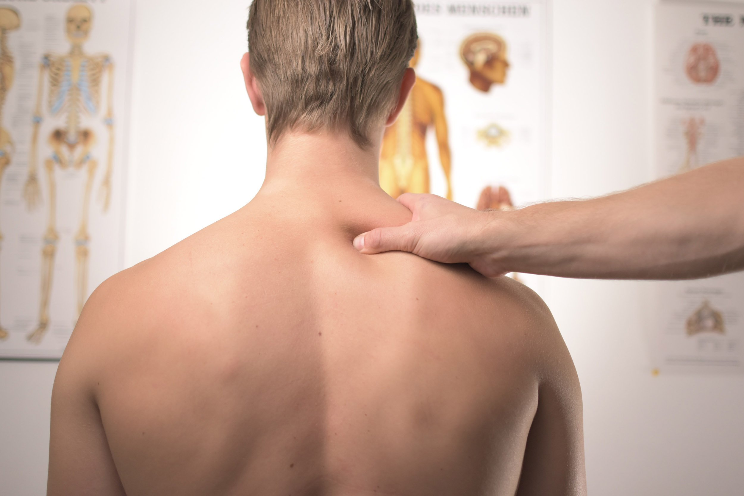 Man getting pressure applied to shoulder area with thumb